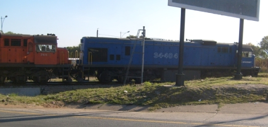 Leading diesel locomotive pulling a train of soda ash cars though level crossing at Magaliesberg