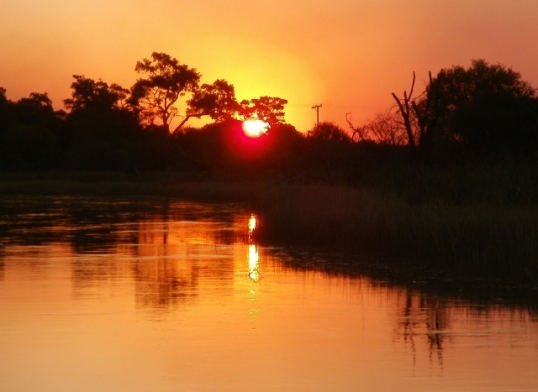 Picture yourself in a boat on a river with tangerine trees and marmalade skies: sunset over the Okavango Delta