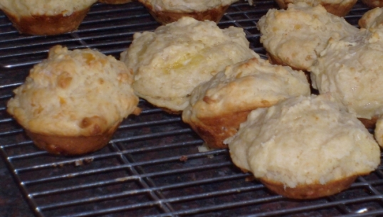 Cheese muffins, baked and ready for eating, either cut in half and buttered, or plain