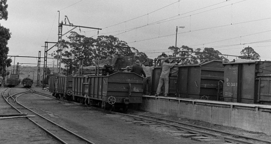 Transferring a load of poles from the narrow gauge to a mainline train at Umlaas Road, 8 December 1980