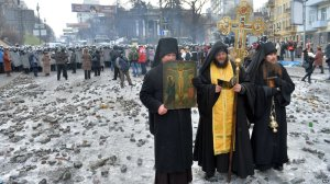Monks and priests pray between protesters and police in Kiev