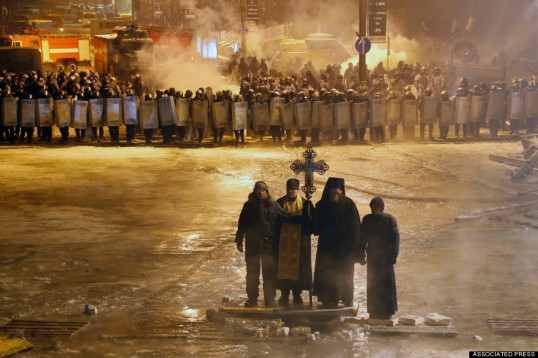 Clergy and monks pray as they stand between demonstrators and riot police in Kiev