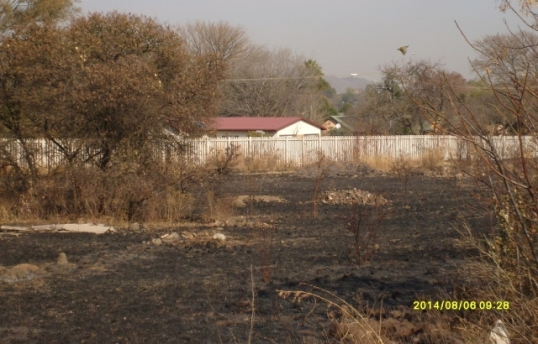 That's our house with the red roof, seen from the railway embankment, with nothing in between but blackened burnt grass/